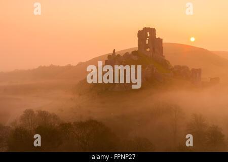 Le soleil derrière le château de Corfe à Dorset Banque D'Images