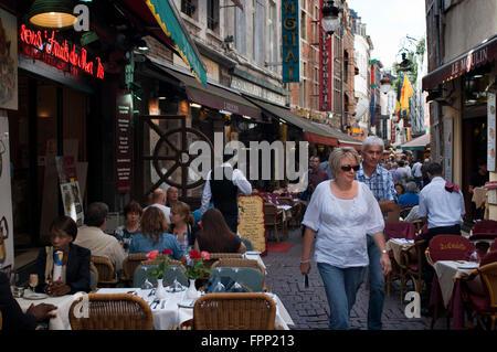 Rue des Bouchers, Bruxelles, Belgique. Un couple dans l'un des nombreux restaurants dans le quartier de l'Ilôt Sacré Banque D'Images