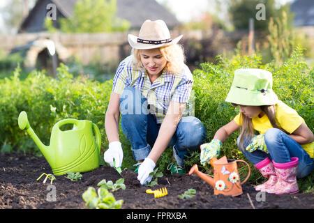 Kid avec mère planter les semis dans le jardin