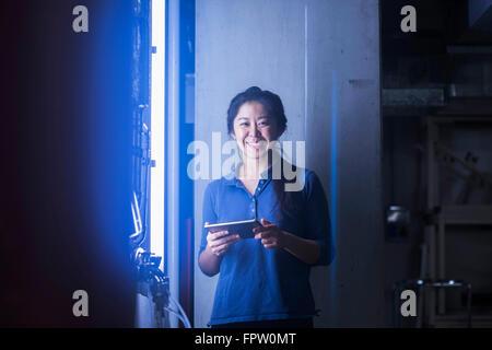 Jeune ingénieur femelle using digital tablet et souriant dans une installation industrielle, Freiburg im Breisgau, Banque D'Images