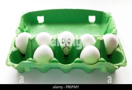 Visage triste part dessiné sur un œuf blanc. L'oeuf se trouve dans un carton vert entouré d'autres oeufs sans visage. Banque D'Images