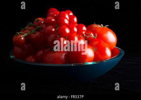 Une clé faible image spectaculaire d'un bol de tomates sur un fond noir Banque D'Images