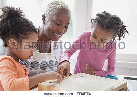 Grand-mère regardant faire granddaughers cookies Banque D'Images