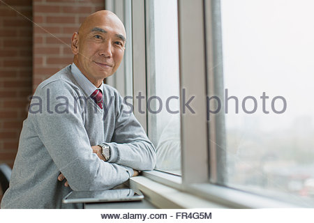 Portrait of senior Asian businessman à fenêtre. Banque D'Images