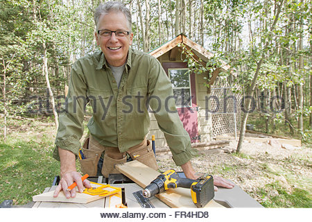 Homme d'âge moyen à l'aide d'outils électriques à l'extérieur Banque D'Images