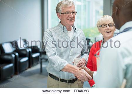 Rencontre couple médecin en salle d'attente Banque D'Images