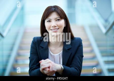 Portrait confident businesswoman sitting on stairs Banque D'Images