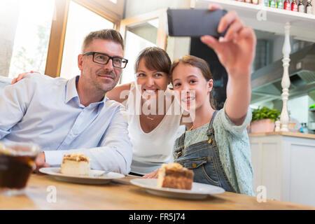 Famille avec le dessert en tenant à selfies cafe table Banque D'Images