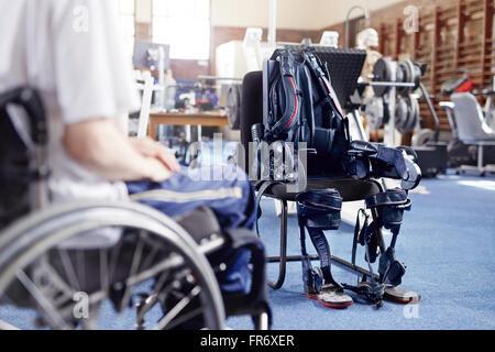 L'homme en fauteuil roulant près de l'appareil de thérapie physique Banque D'Images