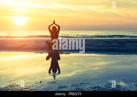Yoga Silhouette femme assise sur la plage avec la réflexion dans l'eau au coucher du soleil. Banque D'Images