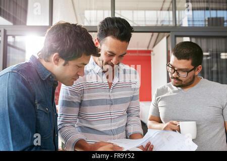 L'équipe de créatifs de travailler sur leur projet d'entreprise ensemble au bureau. Trois jeunes hommes à la recherche Banque D'Images
