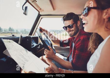 Happy young couple avec une carte dans la voiture. Smiling man and woman using map sur roadtrip. Banque D'Images