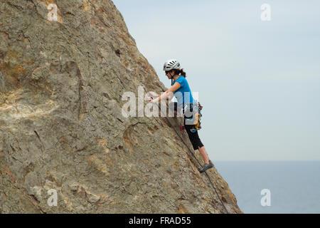 Female rock climber scaling le côté de falaise Banque D'Images