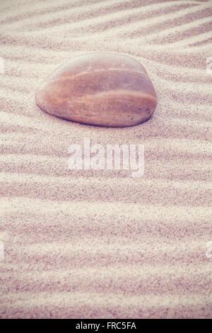 Pierre aux tons Vintage sur les vagues de sable, la nature, l'harmonie, zen ou spa concept background, faible profondeur Banque D'Images