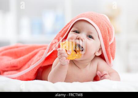 Mignon bébé avec dentition sous une serviette à capuchon après bain Banque D'Images