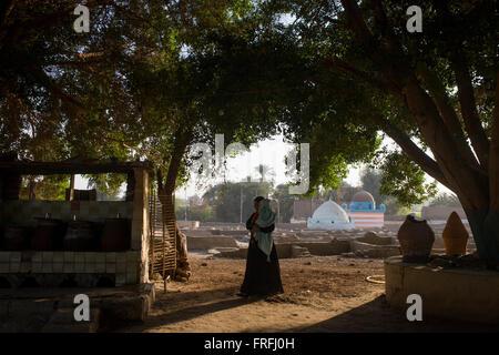 Une femme marche dans la lumière du soleil du soir dans un cimetière local dans le village de Qom (Koom), sur la Banque D'Images