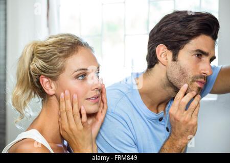 L'homme et la femme contrôle de leur peau dans la salle de bains Banque D'Images