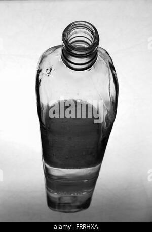 Le flacon en verre à moitié rempli d'eau sur le miroir Banque D'Images