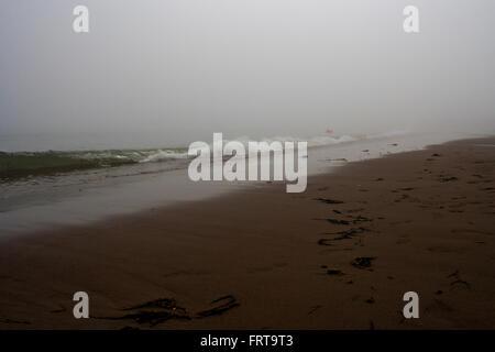 Les vagues se briser sur la plage de sable rouge un jour brumeux. Banque D'Images