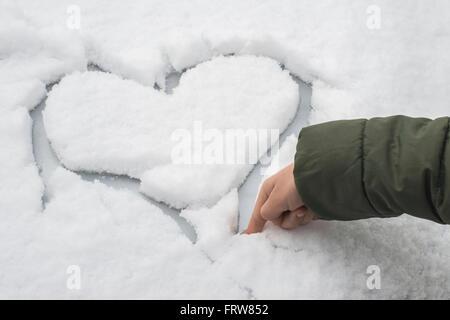 Doigt de petit garçon taille un cœur dans la neige sur une voiture Banque D'Images