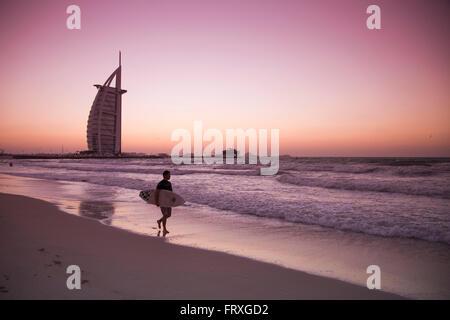 Surfer à marcher le long de la plage près de l'hôtel Burj al Arab au coucher du soleil, Dubaï, Émirats Arabes Unis Banque D'Images