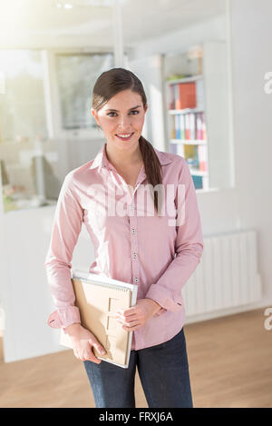 Portrait of a smiling woman standing en face de son bureau. Elle porte un jeans et chemise rose, la tenue des dossiers Banque D'Images