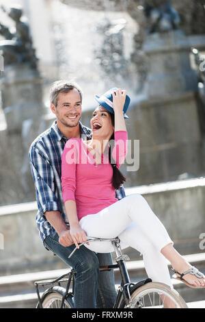 A smiling couple est monté sur un vélo rétro dans le centre-ville. Les cheveux gris l'homme n'est faire du vélo Banque D'Images