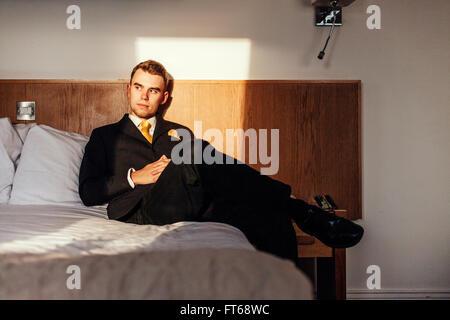 Businessmanman réfléchis bien habillés sitting on bed in hotel room Banque D'Images