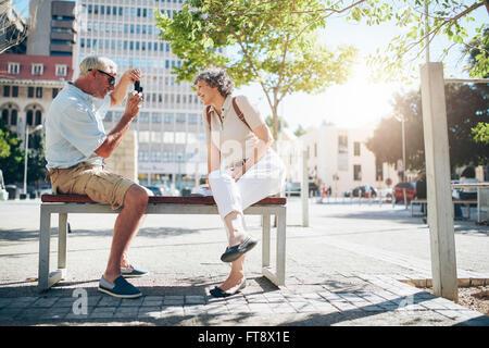 Vue latérale d'être libre de prendre des photos pendant les vacances. D'âge mûr assis dehors sur un banc en photographiant Banque D'Images