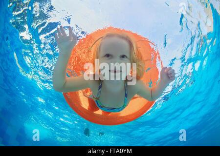 Drôle de photo sous-marine natation bébé fille avec plaisir sur tube orange clair et la plongée dans la piscine Banque D'Images
