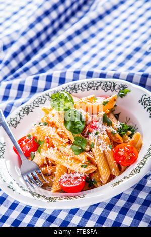 Plaque avec pene pâtes sauce bolognaise tomates cerise haut de persil et les feuilles de basilic sur nappe bleue Banque D'Images