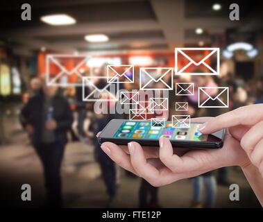 Smart phone émettant une image holographique les icônes de médias sociaux. Toucher la main touch smart phone, social media concept. Arrière-plan de la ville floues.