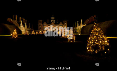 Blickling Hall, Norfolk, Angleterre, décoré avec des arbres de Noël étincelante dans la nuit Banque D'Images