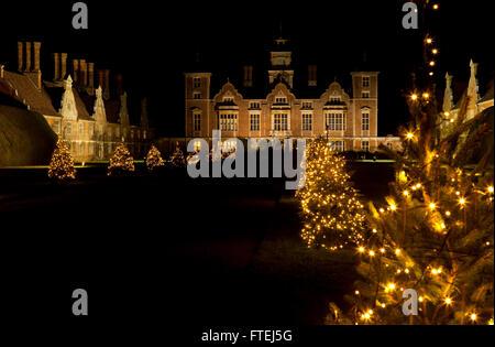 Blickling Hall, Norfolk, Angleterre Royaume-Uni dans la nuit avec un clin d'arbres de Noël Banque D'Images