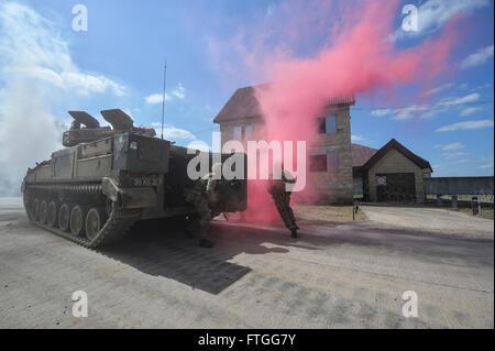 Une unité d'infanterie entouré par la fumée sortir d'un véhicule de combat d'infanterie Guerrier au cours de l'exercice Lion grève.