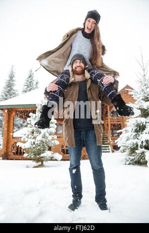 Beau jeune couple s'amusant près de Log Cabin en hiver Banque D'Images