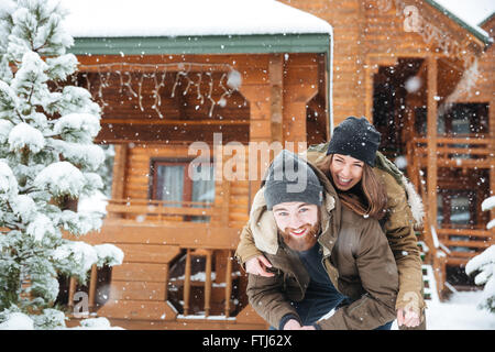 Belle cheerful young couple having fun in front of log cabine en hiver Banque D'Images