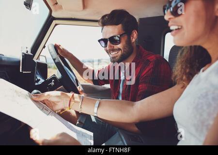 Jeune homme conduisant la voiture avec femme tenant une feuille de route. Jeune couple on road trip.