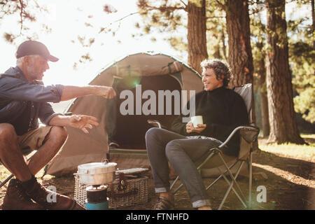 Portrait of senior les campeurs ayant un bon moment au cours d'un voyage de camping sur une journée d'été. Smiling mature couple assis dehors tente