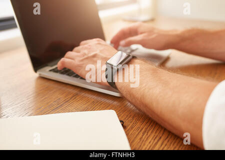 Close up image de l'homme avec une smartwatch working on laptop alors qu'il était assis à son bureau. Banque D'Images
