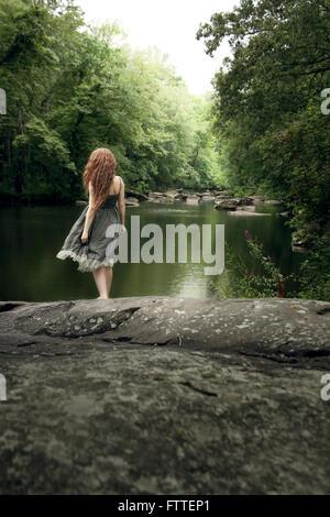 Femme en robe longue soleil au lac