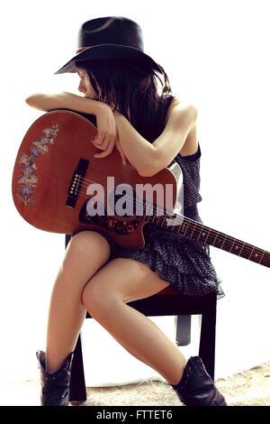 Brunette sitting, de repos à la guitare Banque D'Images