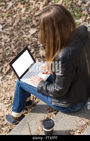 Vue de dessus de jeune femme à l'aide d'un ordinateur portable avec écran blanc assis sur des escaliers. Maquette Banque D'Images
