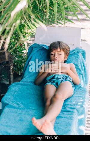 Le garçon endormi sur une chaise longue sur la plage Banque D'Images