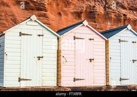 Beach Hut ligne dans des couleurs pastel, red rock fond, dans le sud du Devon, UK Banque D'Images