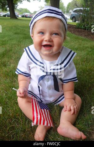 Bébé habillé en marin avec le drapeau américain sur le quatrième juillet Banque D'Images