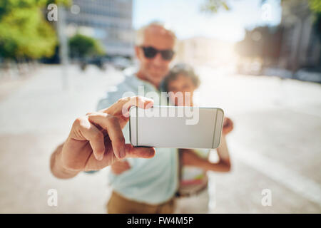 Happy senior couple embracing et prendre un autoportrait sur téléphone mobile à l'extérieur. En tourisme, l'accent sur selfies téléphone mobile.