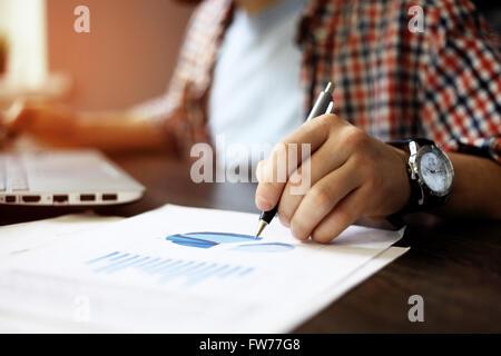 Close up of business man main travaillant sur ordinateur portable avec de l'information affaires graphique diagramme Banque D'Images