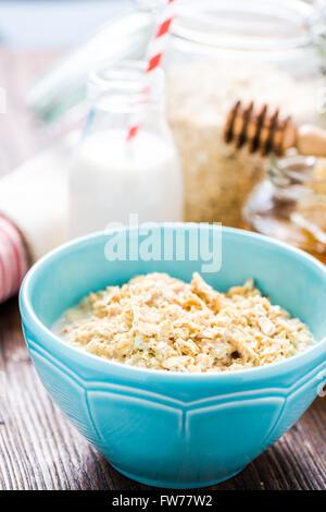 Petit-déjeuner sain, le porridge dans un bol. Pot de miel en arrière-plan Banque D'Images