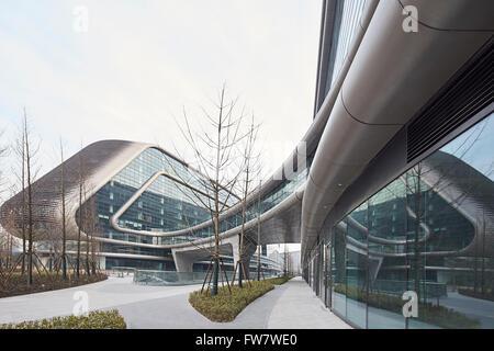 Mur rideau en verre de façade extérieure et des allées paysagers. Sky SOHO, Shanghai, Chine. Architecte: Zaha Hadid Banque D'Images
